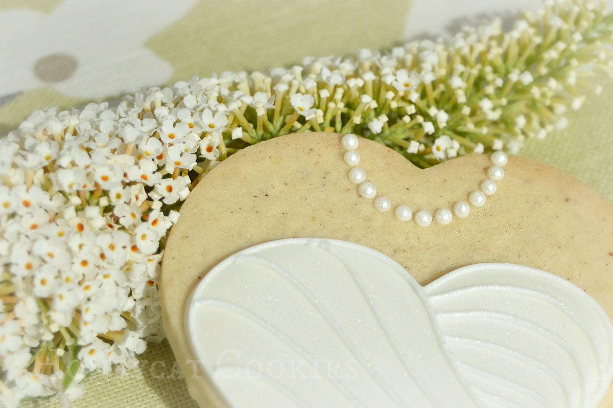 Still life of wedding dress on a heart decorated cookie with flowers, by Honeycat Cookies