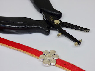 front of bracelet with metal flower and a punch for leather
