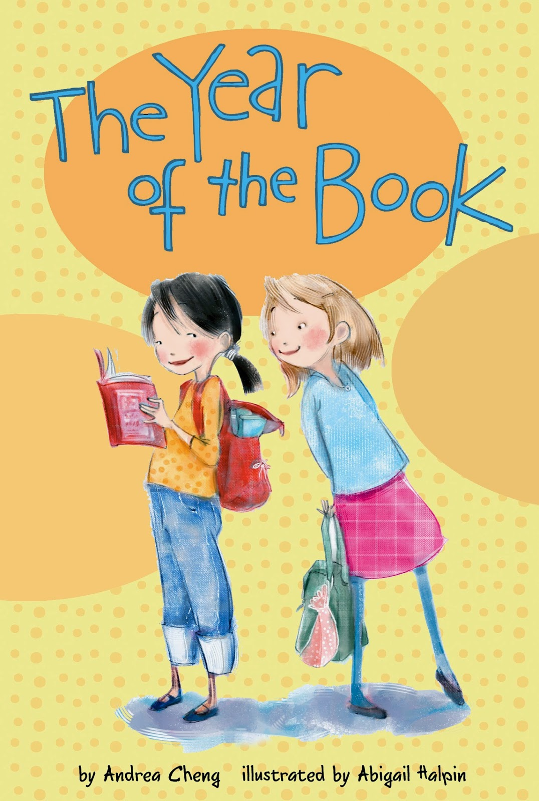 Book cover: Year of the Book by Andrea Cheng. A girl holding a book looks back toward a girl behind her who leans forward as if to see, from over her shoulder, what the first girl is reading.