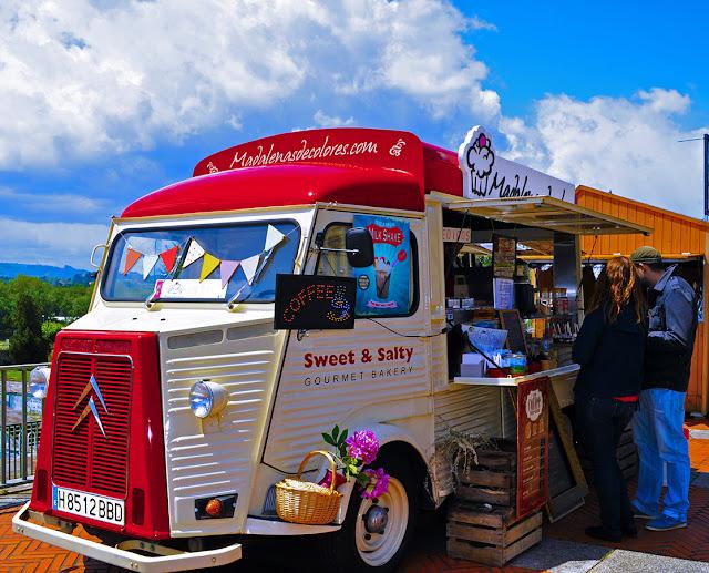camioneta estilo clásico de lechera americana con partes rojas y blancas, decorada con flores, carteles y guirnaldas de banderitas de colores