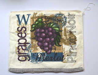 """The folded tea towel is cream in colour with a woven chequered trim on the ends. A deep plum-purple is the contrast colour. On the towel is a printed design of purple grapes with green leaves on a vine. Text around the pictures says """"wine"""". """"grapes"""", """"Pinot Noir"""" and has a round stamp insignia. Other colours in the design include an olive green and a denim blue."""