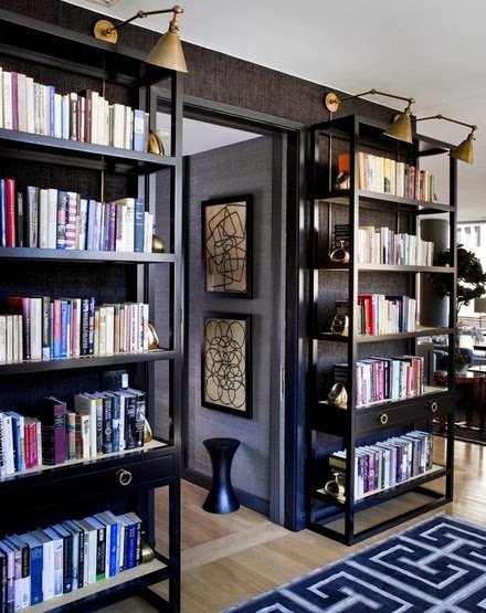 black walls with black bookcases and seagrass wallpaper
