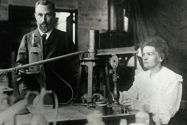 Image: Pierre and Marie Curie in the laboratory, demonstrating the experimental apparatus used to detect the ionsation of air, and hence the radioactivity, of samples of purified ore which enabled their discovery of radium | c:a 1904 | Wikipedia