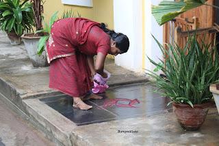 A woman drawing Kolam at the entrance