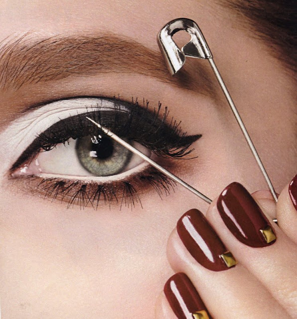 shot of someone using a safety pin to separate eye lashes
