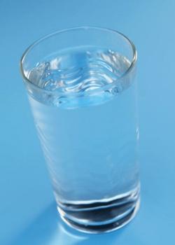 verre d'eau plein sur fond bleu