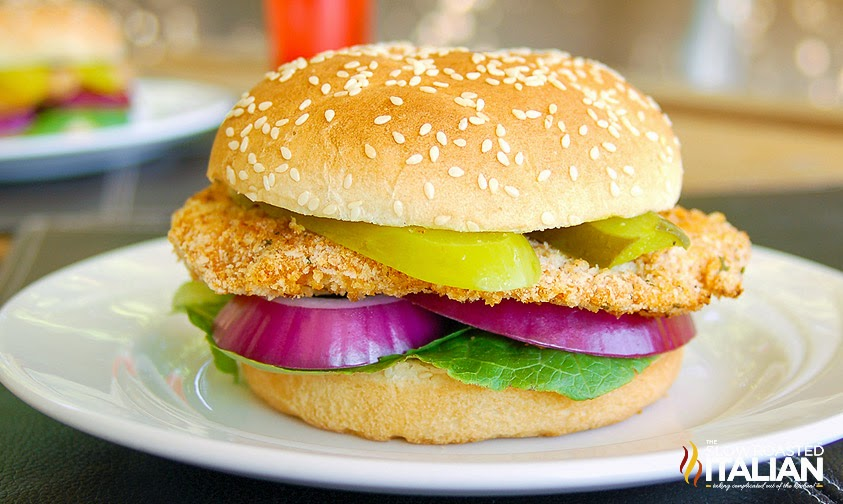 crispy chicken sandwich on sesame seed bun sitting on white plate