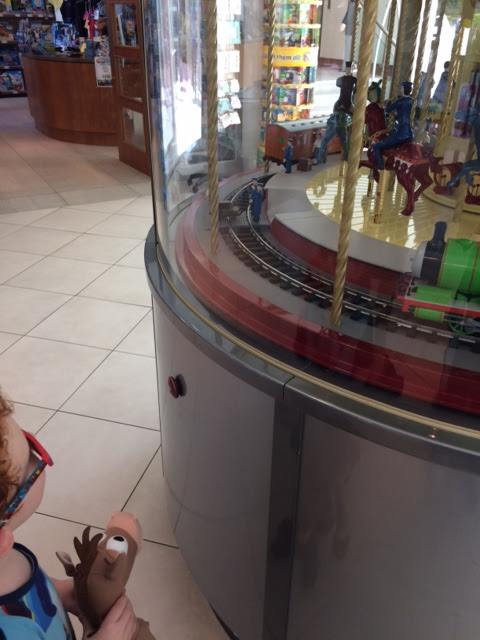 Little boy watching a miniature Thomas themed carousel