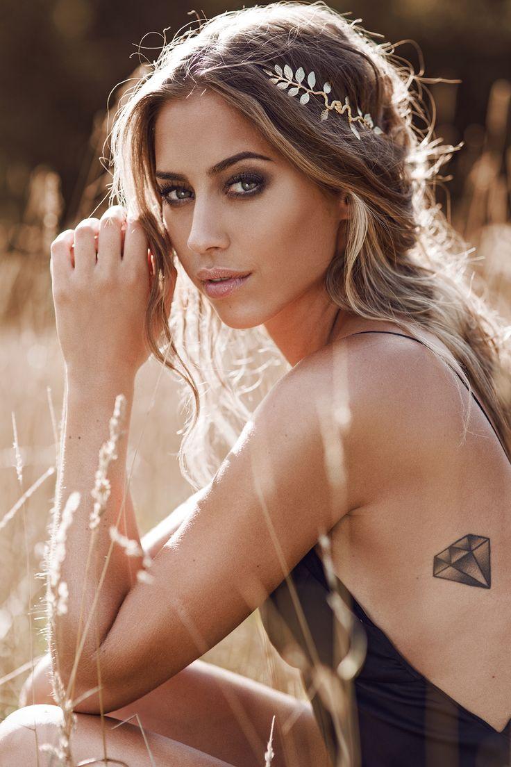 Mujer en medio del campo con diadema de flores, lleva tatuaje de diamante en las costillas