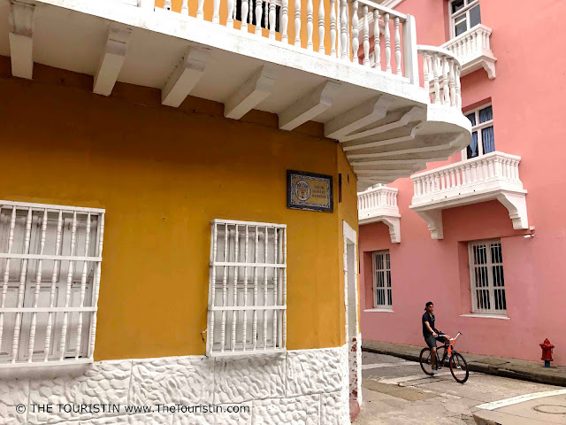 Pink and yellow houses with white balconies and a male cyclist on the road