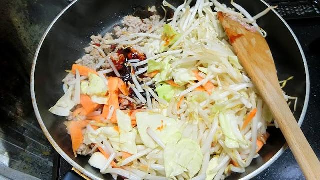 野菜と調味料を炒め合わせる