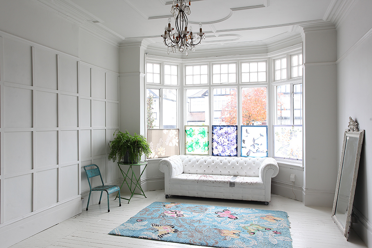 white bohemian interior design with a white couch and large windows