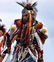 Tüylerle ve renkli kumaşlarla kendini süslemiş olan bir Kızılderili