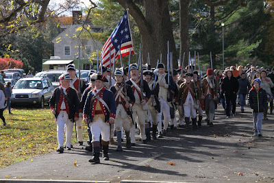 American Revolution reenactors in formation with flag at Hope Lodge