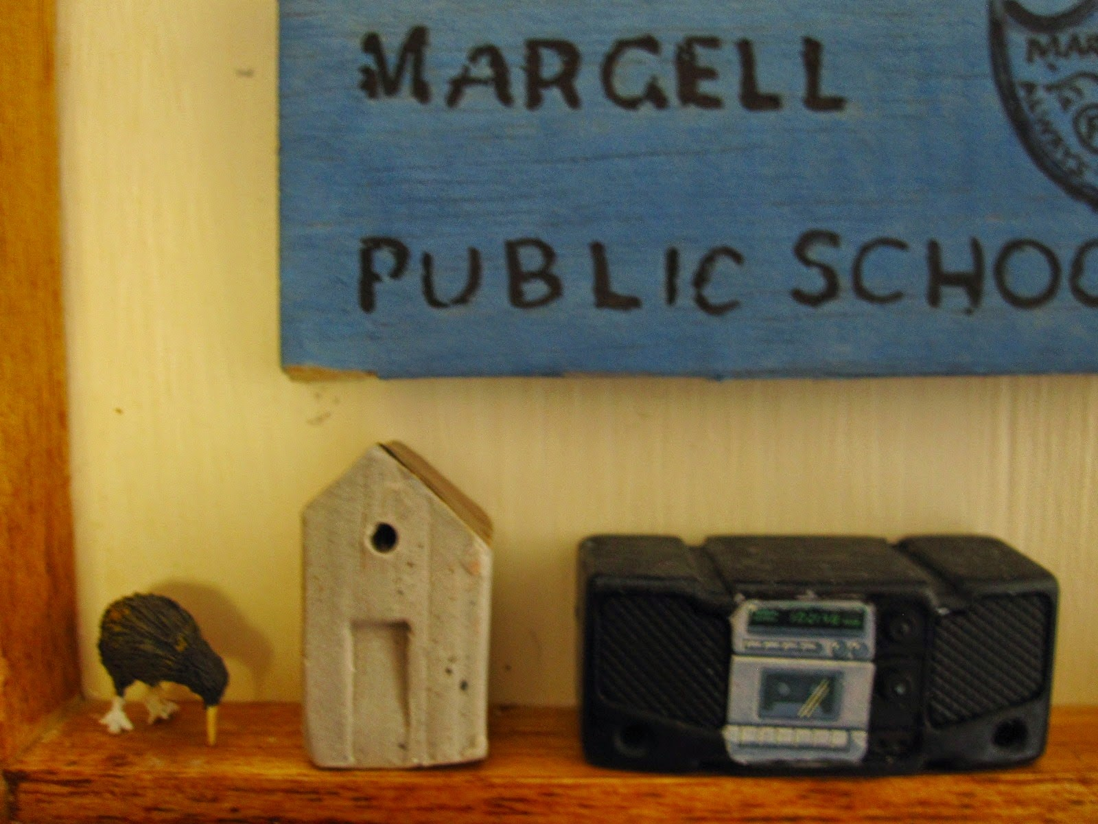 A small clay house displayed in a dolls' house between a kiwi figure and a portable tape deck and CD player.
