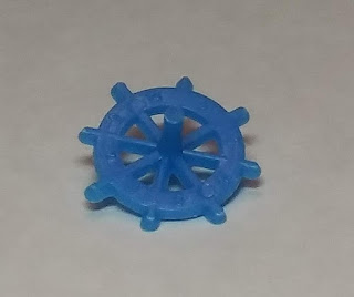 A small blue plastic top, of the type that often comes as a prize in cracker jack boxes. The horizontal part of the top looks like the steering wheel of a pirate ship, with eight spokes running from the centre to extend beyond the circle. It's hard to see, but there are raised numbers on the wheel between each spoke.