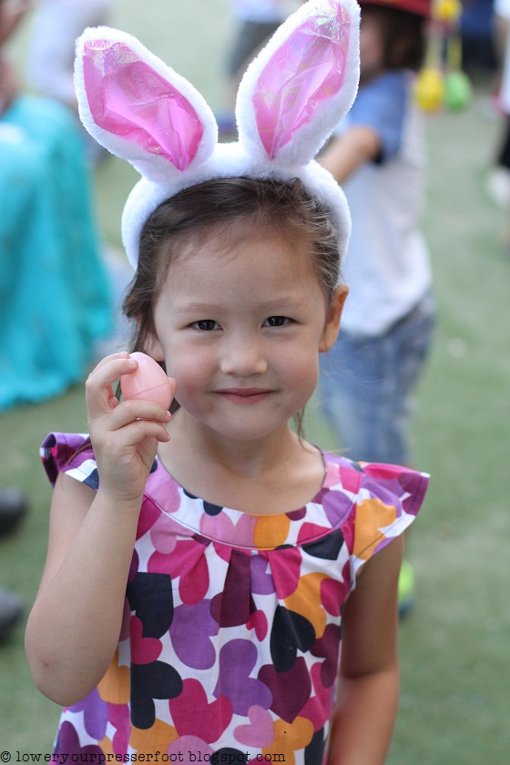young girl wearing rabbit ears holding an easter egg