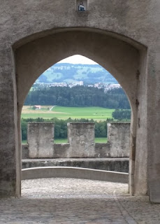 View of the valley through an opening in the wall of the old town, Gruyères, Switzerland