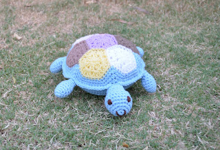 Crocheted patchwork turtle on the lawn. The turtle's body, leg and head are light blue with a patchwork of hexagons on the shell on its back.