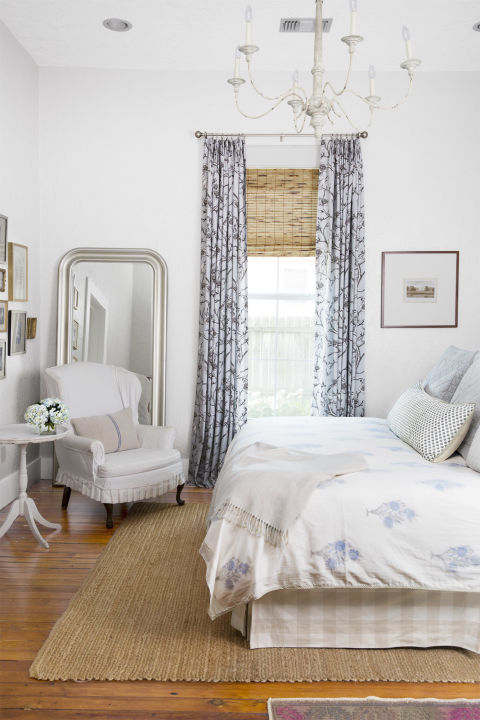 Beautiful bedroom with blue decor in a charming cottage in Texas with interior design by Holly Mathis. Blue print churtains, a natural jute rug over pine floors, and a cozy cottage style arm chair star in the winning mix. #bedroom #decorating #bluebedroom #farmhouse #cottage
