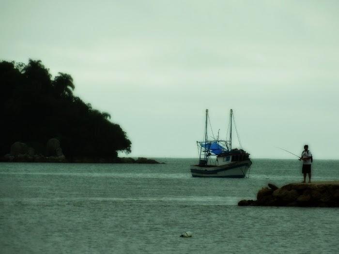 Pescador no trapiche (à direita, na foto),  barco e Ilha de Porto Belo (à esquerda)