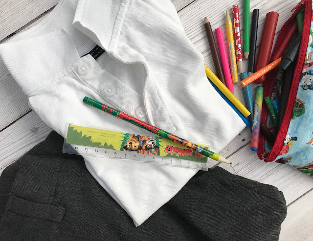 A folded school uniform with crayons, pencil case, pencil and ruler laid on it and around it