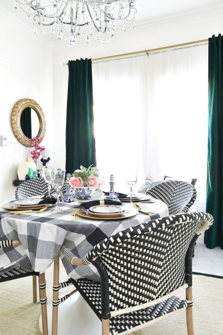 Green velvet curtains add color to a black, white and gold decorated dining room with alabaster white walls and bistro dining chairs.