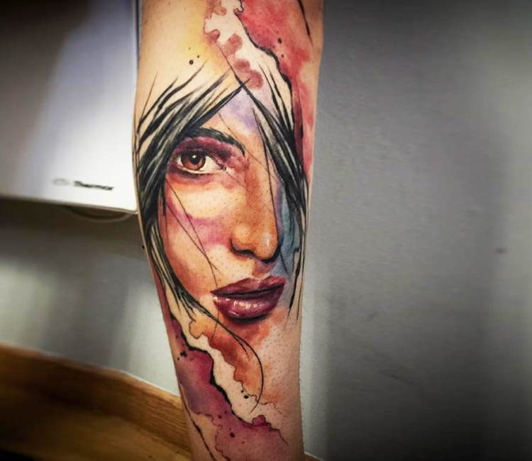 Tatuaje de un rostro de mujer melancólica en acuarelado