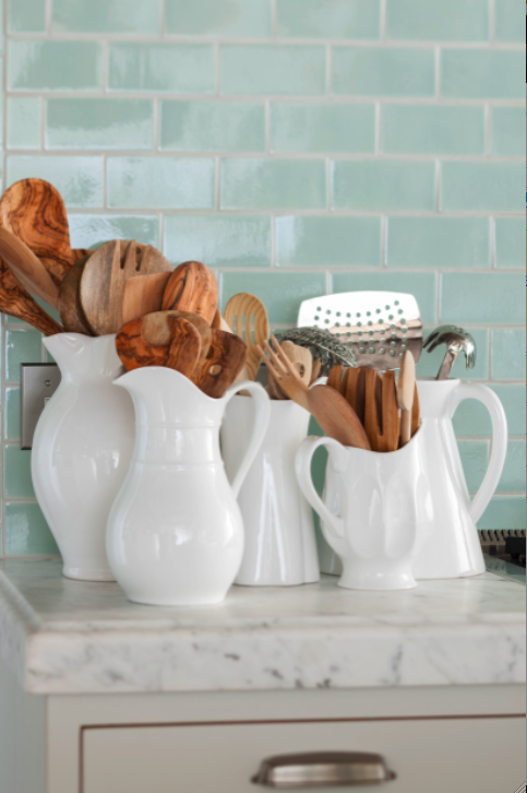 qua or green subway tile and white pitchers in a kitchen. Come see this Rustic Elegant French Gustavian Cottage by Decor de Provence in Utah! #frenchcountry #frenchfarmhouse #interiordesigninspiration #rusticdecor #europeanfarmhouse #housetour