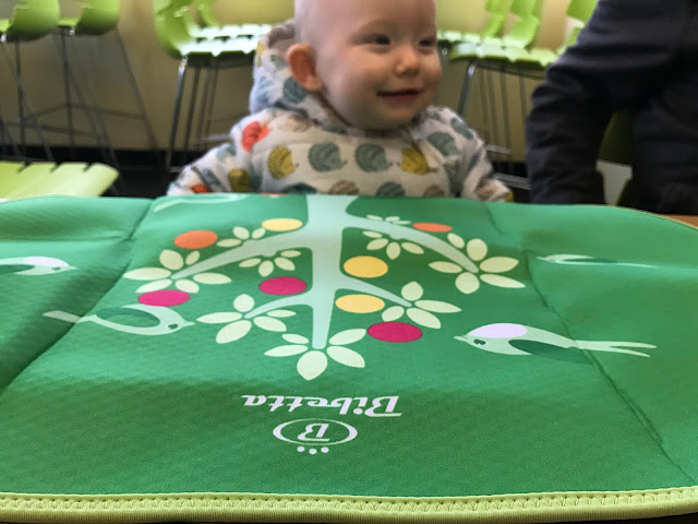 A photograph of the Bibetta placemat with the focus on the logo nearest the camera and with a baby sitting in the background