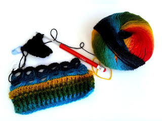 A ball of rainbow coloured yarn on the right hand side with two small samples linked to it by a dark section of yarn. The largest sample starts with light blue to green to yellow horizontal striped ribbing above which are two rows of broomstick eyelets in light blue and dark blue.  Following on from that sample, attached by a length of dark yarn, a sample of darkest blue post stitch ribbing. The crochet hook is still inserted into the active loop at the top of the dark sample. The hook is powdercoated aluminium with a red plastic handle. There is a white label attached with the size '2.50 mm' printed on the label. The size '2.5 mm' is also embossed on the side of the red handle in fine white lettering.