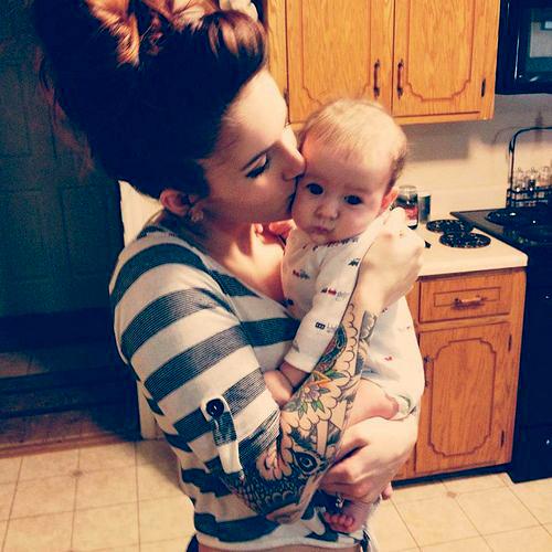 Madre tatuada besando a su bebe