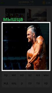демонстрация мышцы мужчиной с голым торсом на сцене