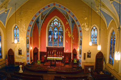Photo from mezzanine of red painted apse with pulpit, crucifix and stained glass ecce homo window.