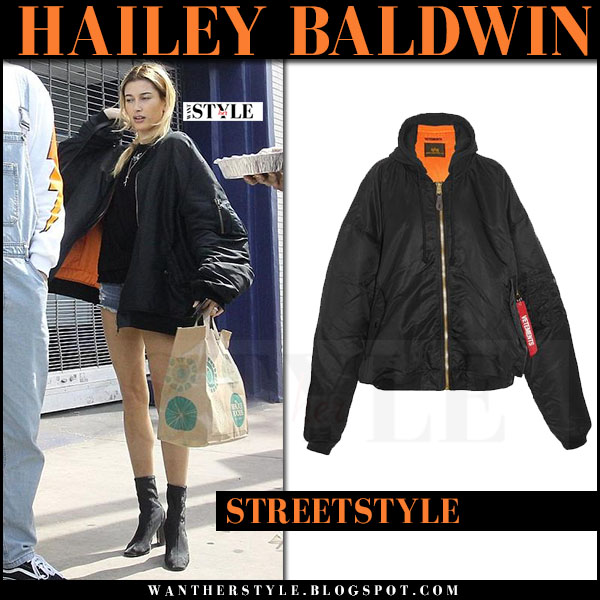 Hailey Baldwin in black oversized bomber jacket vetements, denim shorts and black boots what she wore march 2017