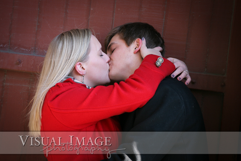 Engaged couple kissing in alley