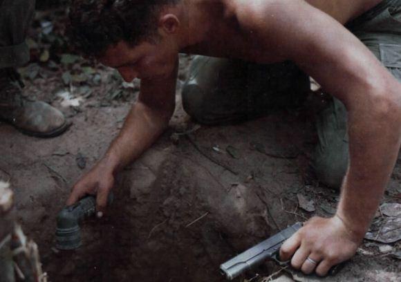 Tentara AS memeriksa lubang Viet cong