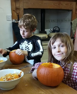 Picture of my two children carving Halloween pumpkins at the kitchen table