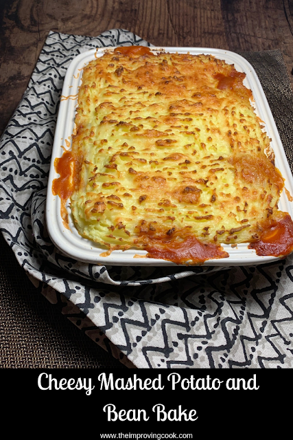 A casserole dish of Cheesy Mashed Potato and Bean Bake on a beige patterned tea towel