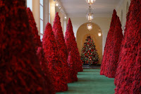 Large Christmas trees completely covered in red cranberries on a green carpet with a traditional Christmas tree in the background. This is in the White House.