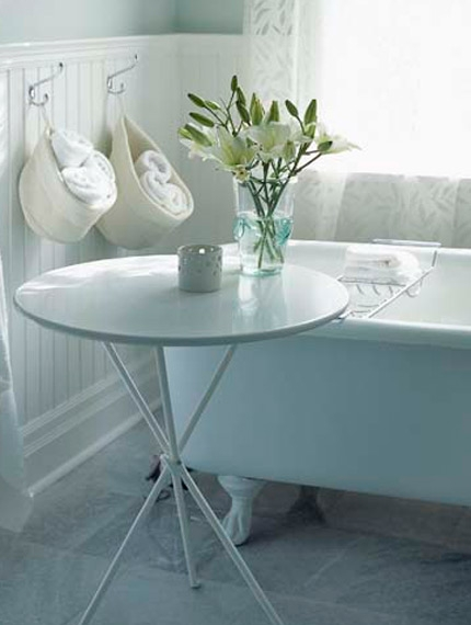 Serene white bathroom with beadboard walls and clawfoot tub