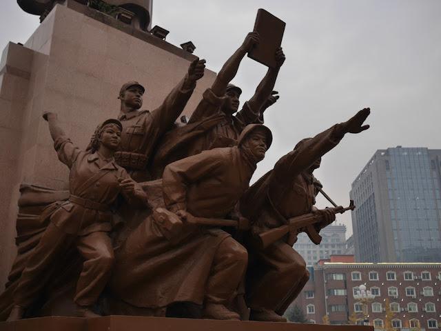 figures surrounding the Mao Zedong statue in Shenyang, China