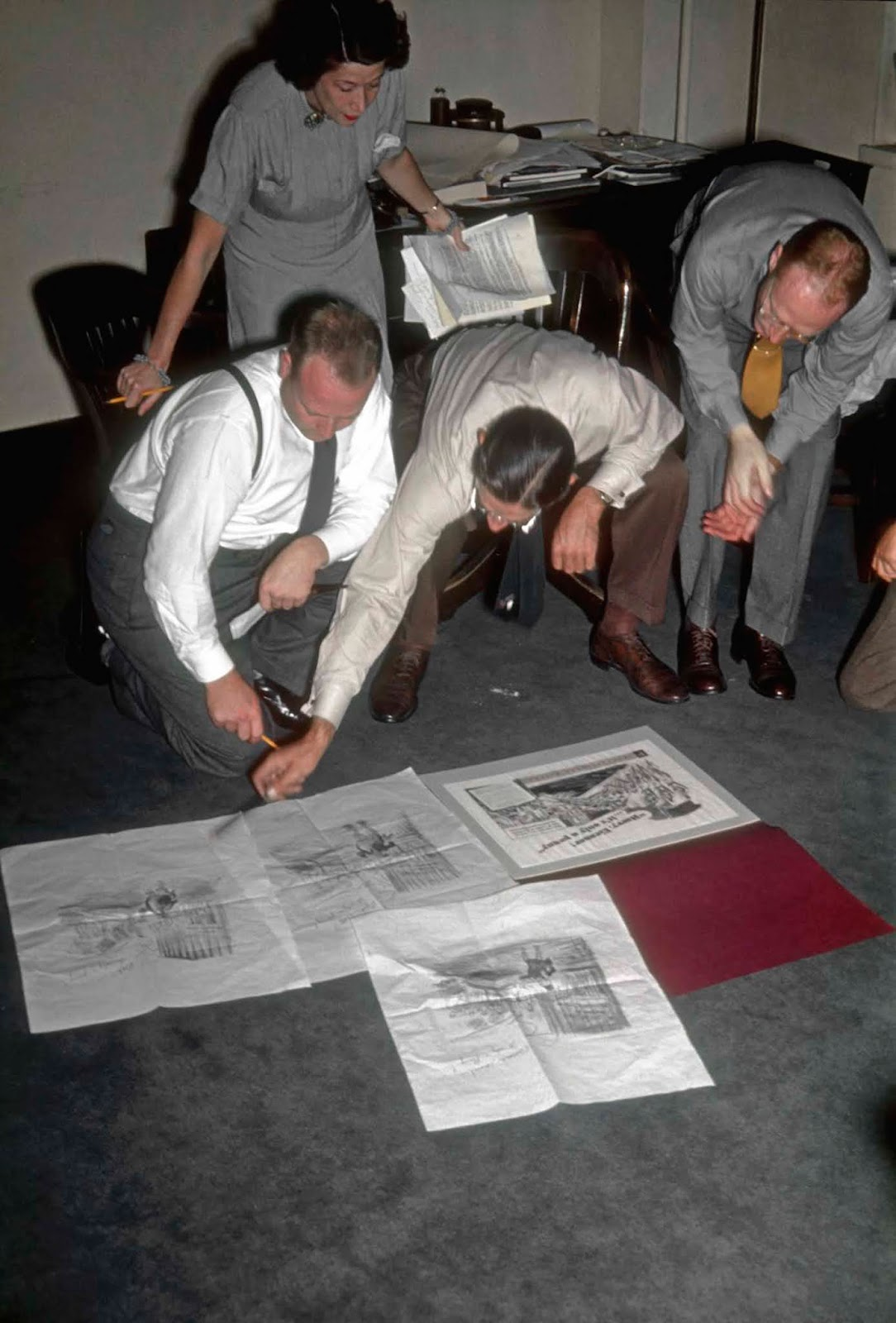 A female secretary clutches a multitude of notes, as three men examine a range of illustrations.