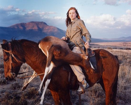 Retrato de una joven mujer cazadora. Sobre un caballo sostiene un ciervo muerto. Se encuentra en un pradera con montañas de fondo.