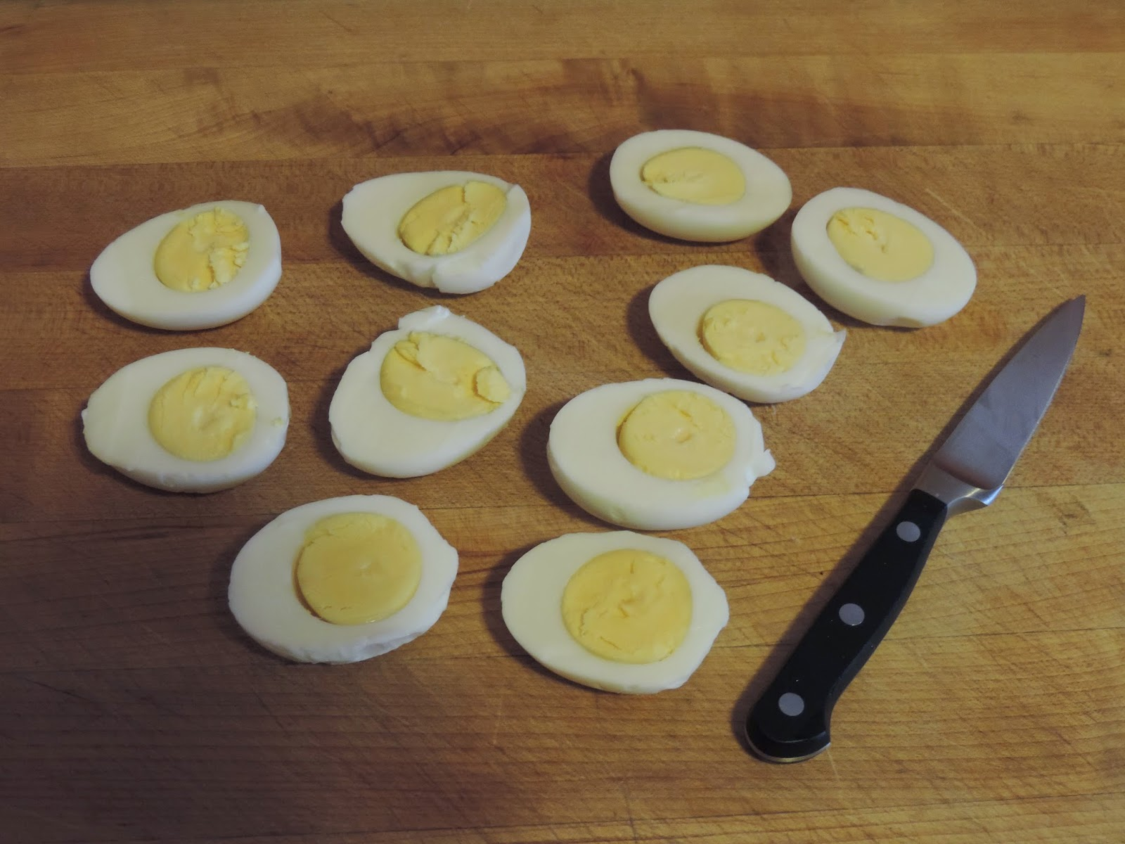 The hard boiled eggs cut in half and placed on the cutting board.
