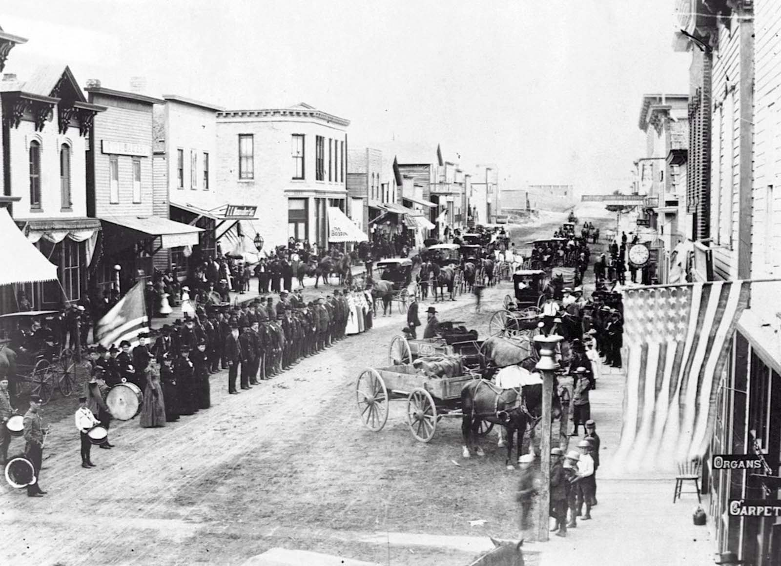 Civil War veterans on Fourth of July, or Decoration Day, on review on the main street of Ortonville, Minnesota. 1880.