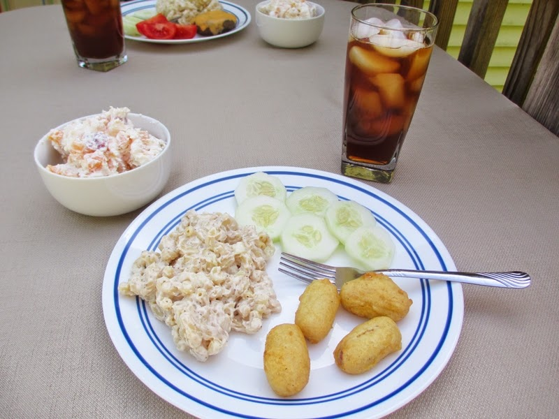 Plate of food, bowl of fruit salad, and glass of iced tea.