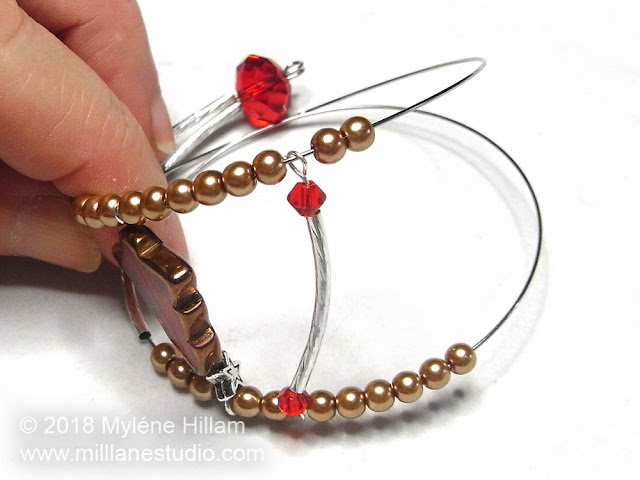 Two coils of memory wire strung with a hollow tube component and glass pearls.