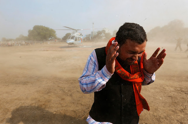 Image Attribute: A supporter covers himself from the rising dust caused by the helicopter of Keshav Prasad Maurya, the Uttar Pradesh state's president for the ruling Bharatiya Janata Party (BJP), during an election campaign rally in Bah, in the central state of Uttar Pradesh, India, February 2, 2017. REUTERS/Adnan Abidi
