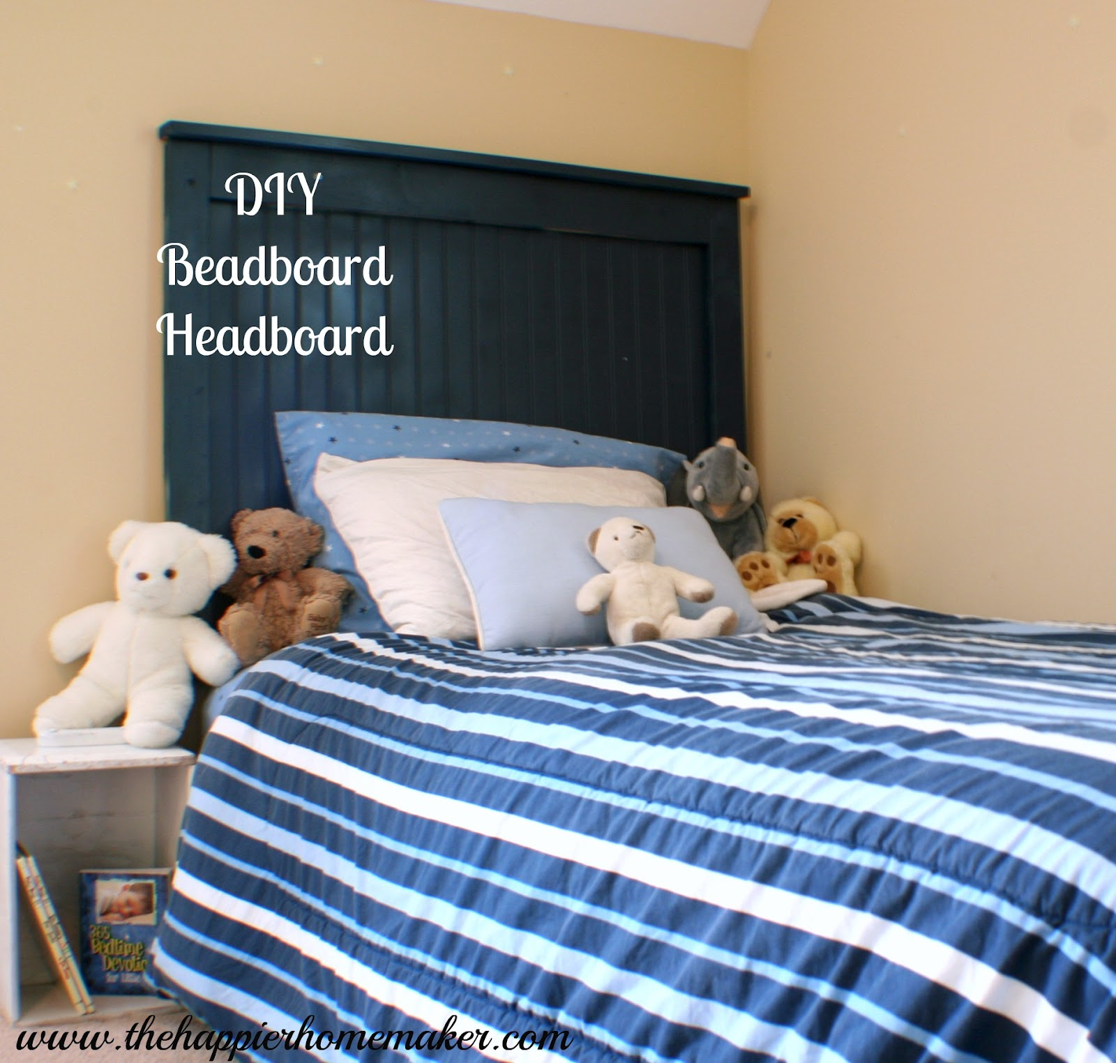 side view of navy blue twin sized diy beadboard headboard with blue striped bedding and stuffed animals